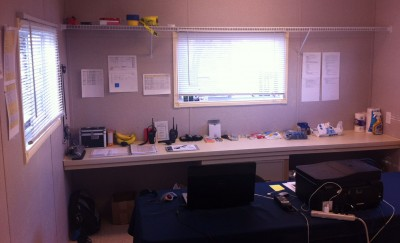 One of the 12 x 12 offices in a 12 x 56 class trailer with timelines and other festival documents posted on the walls.