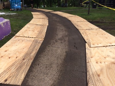 Plywood flanks a backstage access road after a rainstorm